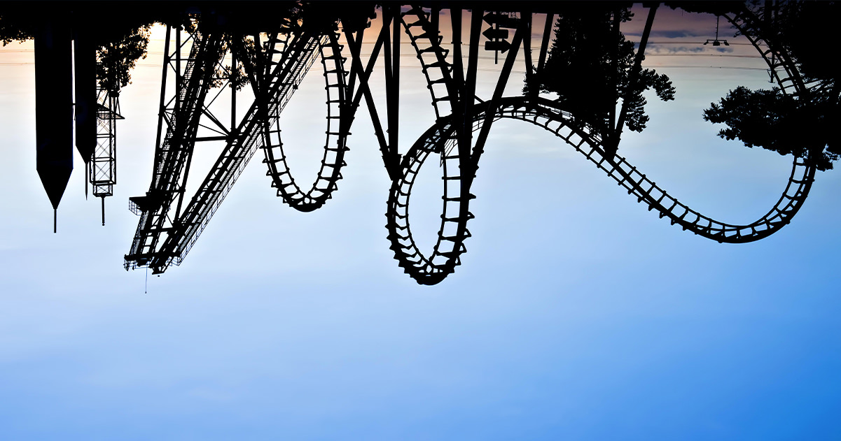 An upside down sunset photo of a rollercoaster