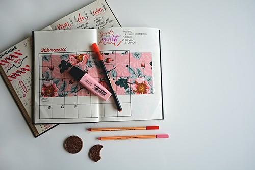 Pink highlighters and pens over a bullet journal showing a calendar view, alongside some biscuits, one with a bite taken out of it.