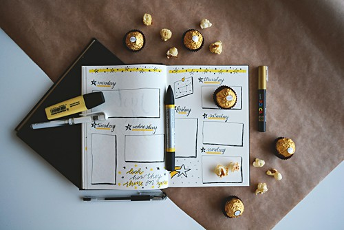 Table top view of a bullet jrouanl with sweets and perfect stationery