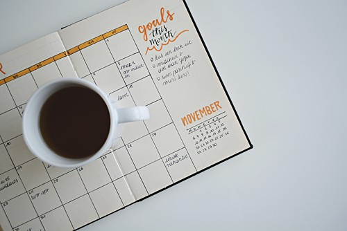 A coffee mug resting on top of a bullet journal, open on the calendar page with the months goals